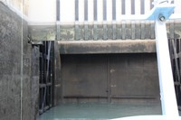Water leaving the lock reveals the lock gates behing the buffer wall