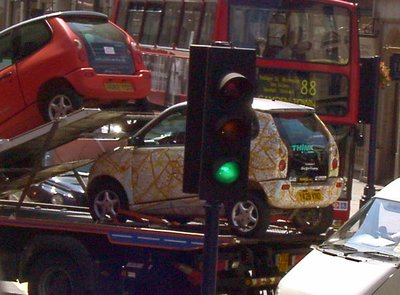 Think car with map of London on a tow truck