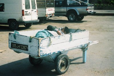 A man taking nap under a sun, outside suuq of Sfax