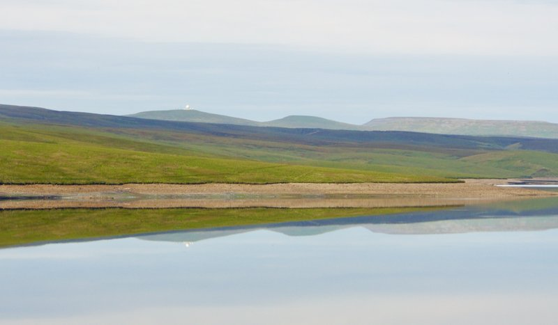 Cow Green Reservoir with view of the observatory in the background reflected in the water