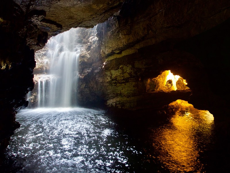 Smoo Cave with fresh water coming in waterfall and sea water at cave mouth