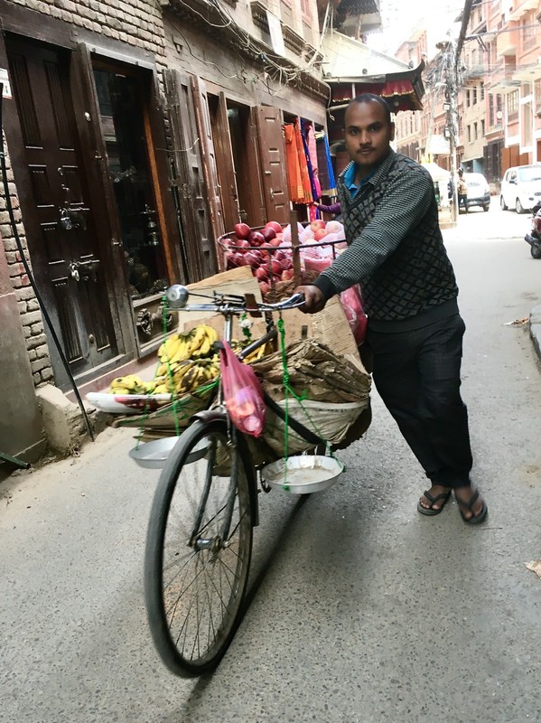 bicycle trader with fruits, veg and scales to weight them