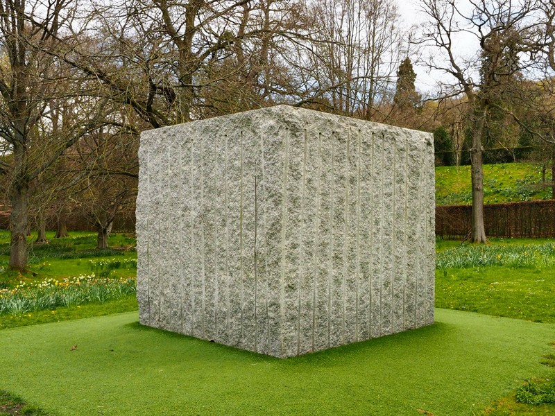 Art sculpture of concrete cube with forest eco system growing inside
