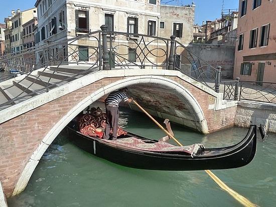 Gondolier ducking under the bridge