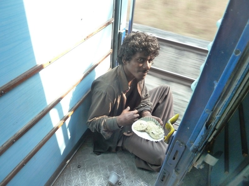 A guy eating by the train door