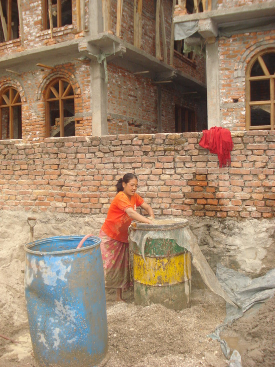 Local Lady making cement with her hands
