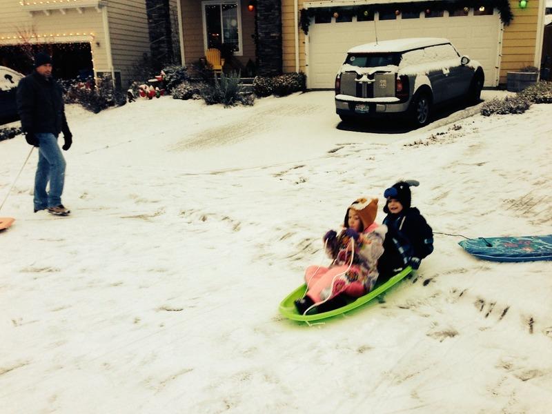 Benaiah sledding in neighbours driveway