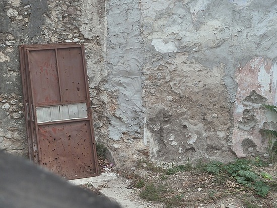Bullet holes in door and wall next to Mirans