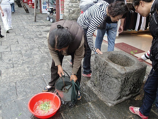 Lady getting water from the well to was her v