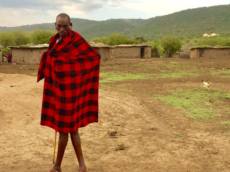 Maasai man in front of his village
