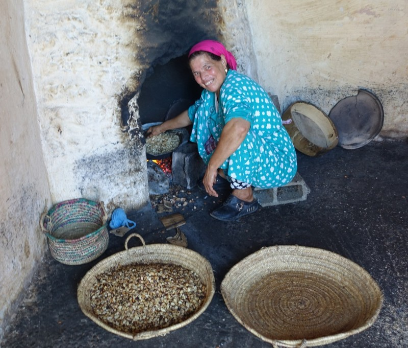 Argan oil production - roasting Argan kernels before grinding to extract oil - very hard work