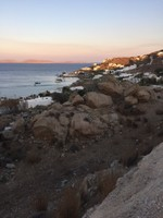 Mykonos in a nutshell - whitewashed buildings, beach, sun lounges, bay and islands, barren and rocky