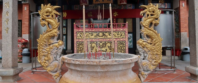 The sand pit for incense sticks is the typical entrance greeting in Buddhist temples.