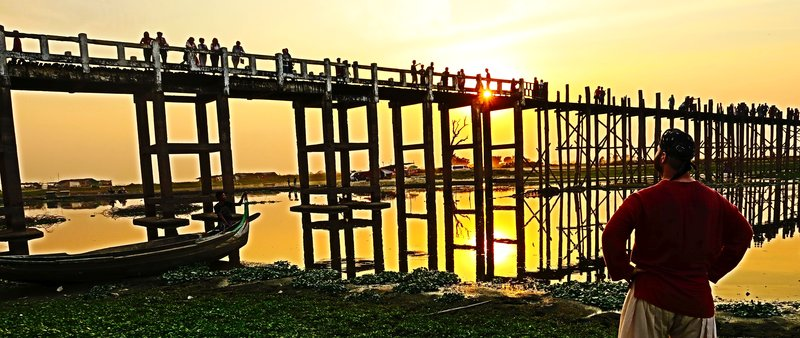 The U Bein teak wood bridge at sunset in Mandalay, Myanmar.