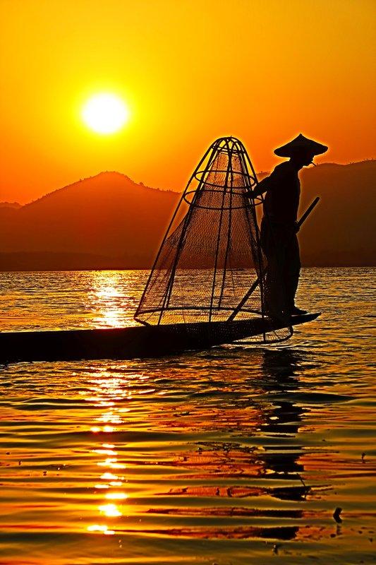 A fisherman at sunset on Inle Lake, Myanmar.