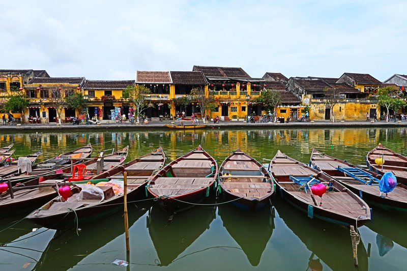 These boats decorated with lanterns ferry couples along the river at night in Hoi An, Vietnam.