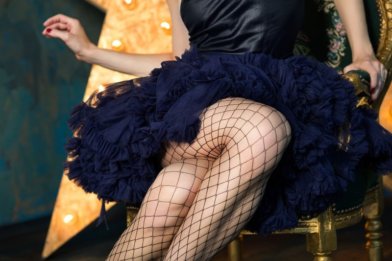 60086921 - beautiful playful woman wearing dark blue lace skirt and mesh stockings posing on chair over dark background with glowing star. legs closeup. actress playing on stage. theatre or dancer.
