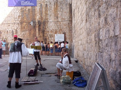 DUBROVNIK  CROATIA.      Buskers , the people are looking at a map of the places bombed in the war.