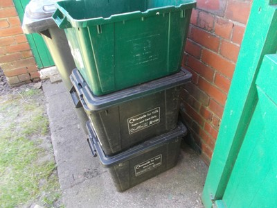 Green box for plastic and tins,  Middle black box for paper and cardboard,  Other black box for glass.