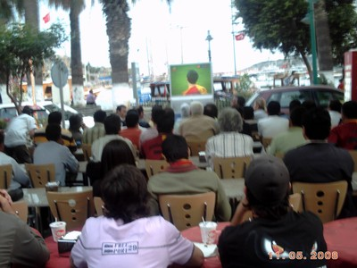 TURKEY  BODRUM.     Watching football on the TV, outside.