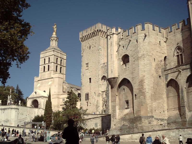 AVIGNON  FRANCE. -- Cathedral with  gold  statue  of  the Virgin  Mary  on  top of  tower.  -- Papal  Palace  to  right.