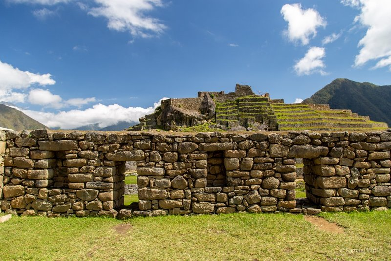 Stone wall with windows in front of Intihuatana pyramid in Machu Picchu
