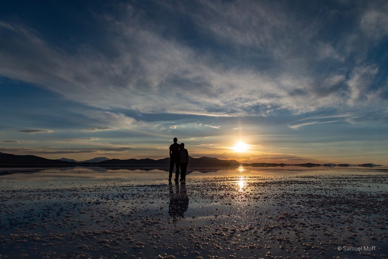 Sam and Marta on the wet Salar de Uyuni in front of the setting sun