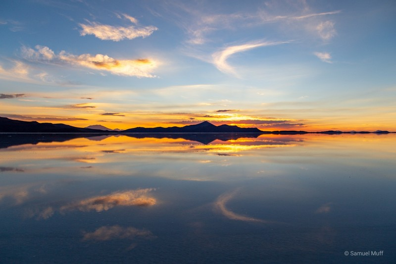Perfect reflection of the colorful sky in the wet Salar de Uyuni after sunset