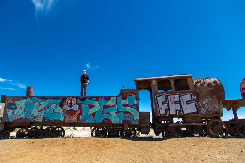 Sam standing on an old train outside of Uyuni