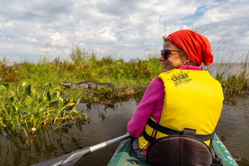 Marta in the kayak with a caiman in front of her
