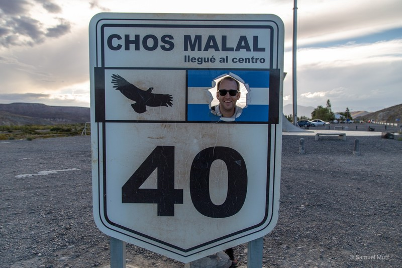 Sam in Chos Malal with the sign marking the midpoint of Ruta Nacional 40
