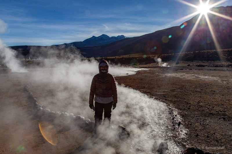 Marta standing next to a fuming stream at the El Tatio Geysers at sunrise