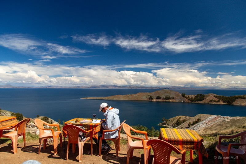 Sam on Isla del Sol with a glass of wine reading our South America guidebook