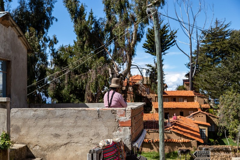 Bolivian woman sitting on her balcony in Yumani on Isla del Sol