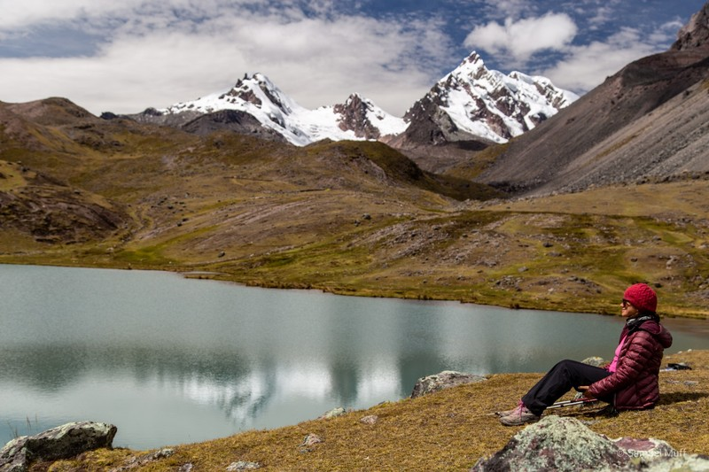 Marta sitting in front of a lagoon and snow-capped mountains