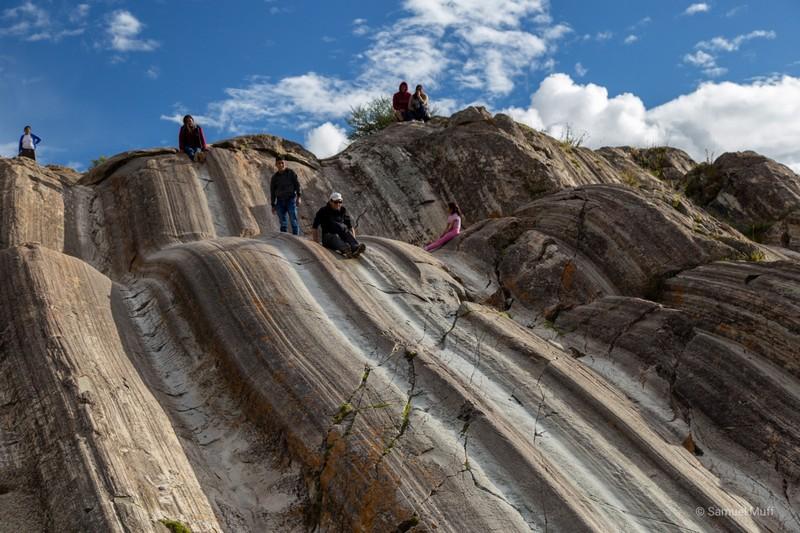 Sam sliding down a rock in Saqsaywaman