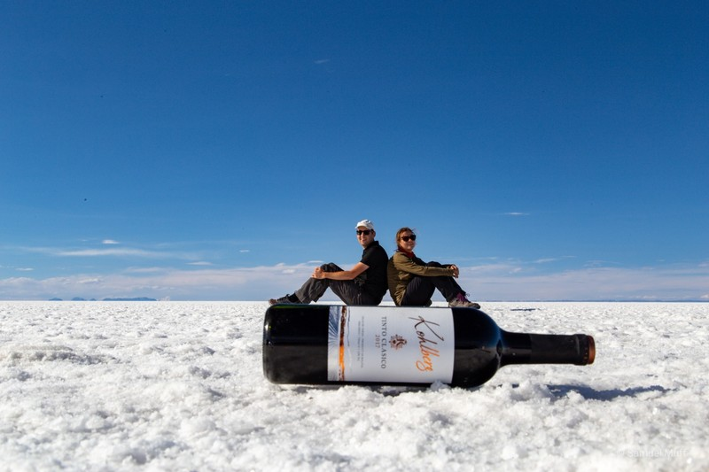 Sam and Marta sitting on a giant wine bottle