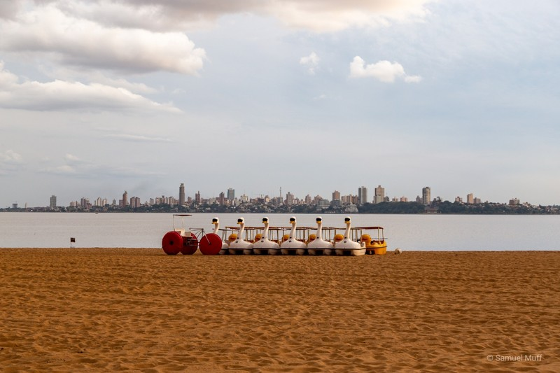 Paddle boats on Playa San José in Encarnación with Posadas, Argentina in the background